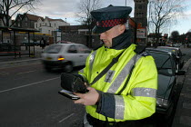 03-03-2004 - Parking attendant writes a parking ticket in a clearway zone for bus route, Bristol © Paul Box