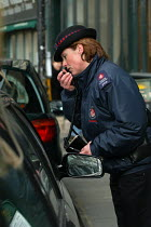 03-03-2004 - Woman parking attendant checking a road Tax disc, radioing into the control centre, Bristol © Paul Box