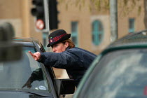 03-03-2004 - Woman parking attendant gives a motorist directions , Bristol © Paul Box