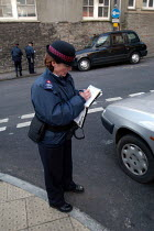 03-03-2004 - A woman parking attendant, issuing a ticket. Bristol © Paul Box