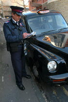03-03-2004 - A newly trained parking attendant writes a parking ticket for a taxi , Bristol © Paul Box