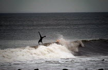 01-03-2004 - A surfer , surfing on the north coast of Devon in the winter. Jumps off weave to avoid rocks © Paul Box
