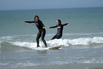 01-03-2004 - Girls learning to surf , Freshwater west, Pembrokeshire. © Paul Box