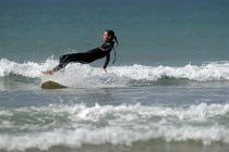 01-03-2004 - A learner surfer falls off her board whilst learning to surf , Freshwater west, Pembrokeshire. © Paul Box