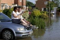22-07-2007 - Local residents share a glass of wine as flood water rises in their flooded estate, Tewkesbury, Gloucestershire after the river Avon and the river Severn bursts their banks. © Paul Box