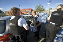 29-07-2007 - Gloucester, Police community support officers put bottles water into cars for people that have no drinking water supplies. © Paul Box