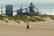 28-09-2004 - Walking the dog on the beach with the Corus steelworks in Redcar behind, North Yorkshire. © Philip Wolmuth
