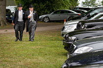18-06-2009 - Two men in top hats pass the expensive cars in the car park at Ascot racecourse. © Philip Wolmuth