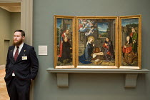 04-08-2010 - Gallery attendant, Nativity painting by Gerard Davi (1455) , Metropolitan Museum of Art, Manhattan, New York. An Early Netherlandish painting of an iconic religious scene The Nativity with Donors and... © Philip Wolmuth