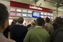 09-12-2011 - Men watch a televised horse race at a Ladbrokes bookmakers counter at Doncaster racecourse. © Philip Wolmuth