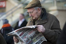 09-12-2011 - A man with a cigar reading the Racing Post - checking the form- before placing a bet at Doncaster racecourse © Philip Wolmuth