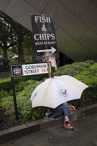 25-08-2015 - Tourist with an umbrella in heavy rain, fish and chips sign City Of London © Philip Wolmuth
