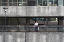 09-23-2015 - Man speaking on a mobile phone outside a City of London office block © Philip Wolmuth