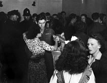 12-03-1949 - Police watch as off-duty American GIs from Burtonwood USAF dancing with local women at the Broadway Club in Warrington. British and American police stage joint patrols to keep an eye on things. The ai... © Elizabeth Chat