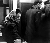 13-03-1949 - Young woman sitting in the corner of the Red Rose milk bar in Warrington looks on as offf-duty American GIs from the nearby Burtonwood USAF airbase talk together at the counter. The airbase was reopen... © Elizabeth Chat