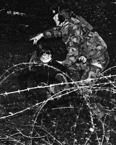 11-12-1983 - Greenham Common. Soldier arrests a woman as she attempts to enter the US air base as part of her campaign of direct action for peace and against nuclear weapons held at the site. © Melanie Friend