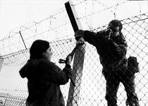 29-10-1983 - Greenham Common. Soldier grappling with woman as she uses bolt cutters to cut the perimeter fence and enter the US Air Base in Berkshire as part of the campaign of peaceful direct action against the h... © Melanie Friend