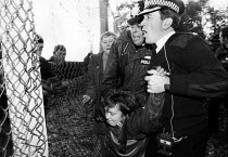 20-10-1983 - Greenham Common. Police officers arrest a woman as she enters the US air base as part of her campaign of direct action for peace and against nuclear weapons held at the site. 1983 © Melanie Friend
