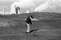 10-01-1977 - Golfer playing a shot with the chimneys of Windscale nuclear power plant in the near distance, 1977, Seascale Golf Course, Cumbria. © Mike Khan