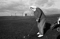 10-01-1977 - Female golfer playing a shot with the chimneys of Windscale nuclear power plant in the near distance behind her, 1977, Seascale Golf Course, Cumbria. © Mike Khan