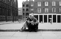 11-07-1962 - Young girl and father sitting in the street, London 1960s © Romano Cagnoni