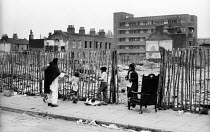 11-07-1962 - Asian mother with her family, post war bombsite 1960s King's Cross. Derelict areas were common features in the poorer parts of London © Romano Cagnoni
