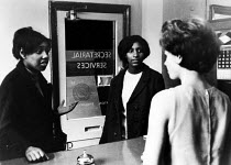 23-08-1965 - Two young black women seeking work London 1965 in a secretarial recruitment office when racial discrimination against ethnic minorities was far more prevalent in society © Romano Cagnoni