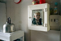 27-12-1999 - A retired man looking into a mirror, on his kitchen wall. © Rob Bremner