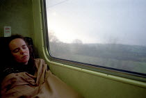 20-12-1999 - A woman sleeping on a train, while traveling to Wick in Northern Scotland. © Rob Bremner