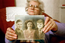 22-12-1999 - Elderly woman holding a photograph of her brothers and herself, that was taken when they were young. © Rob Bremner
