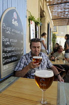 06-08-2011 - Customer drinking a glass of Leffe Beer at a table at a cafe in Arles in southern France. © Stefano Cagnoni