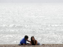 10-09-2012 - Couple enjoying a romantic moment together on the beach at Brighton. © Stefano Cagnoni