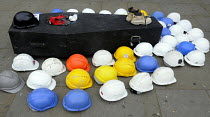 28-04-2014 - Hard hats laid on and beside coffin, symbolising number of workers' lives lost in construction industry in UK past year, Workers Memorial Day commemoration, Tower Hill in London. © Stefano Cagnoni
