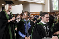 16-07-2014 - Maths Graduands waiting to collect their degrees, as Graduates immediately in front of them look over the degrees they have just received at their Graduation ceremony at the University of Leeds. © Stefano Cagnoni