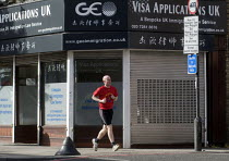 07-05-2015 - Male jogger passing offices advertising its legal advice for Visa Applications, immigration, asylum and human rights issues, Holloway, north London. © Stefano Cagnoni
