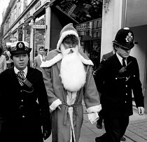 15-11-1984 - Miners Strike 1984 Police arresting Father Christmas (Derek Freeman) arrested for allegedly causing an obstruction outside Hamleys Toy Store in Regent Street, whilst helping to launch an appeal for do... © Stefano Cagnoni