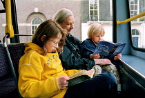 16-10-1999 - Children reading as they travel on the top deck of a bus with their grandmother © Stefano Cagnoni