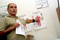 19-03-2004 - Lecturer in Trade Union Studies pointing to a 'bodymapping' chart to explain industrial injuries during a class on Health and Safety for building workers on a Multiplex construction site. © Janina Struk