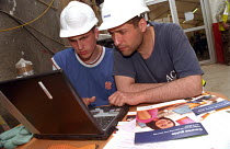 25-05-2004 - Building workers in hard hats on a construction site at Canary Wharf are introduced to a basic skills computer course which is run at the nearby Learning Centre run by the TUC, UCATT and Lewisham Coll... © Janina Struk