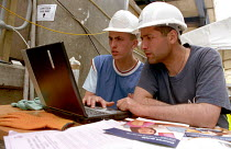 25-05-2004 - Building workers in hard hats on a construction site at Canary Wharf using a laptop and learning about basic computer skills training at the nearby Learning Centre run by Lewisham College, TUC and UCA... © Janina Struk