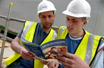 25-05-2004 - Construction workers in hard hats on a building site at Canary Wharf reading a brochure about Learndirect basic skills courses. © Janina Struk