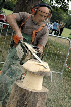 09-09-2007 - Woodcarver with electric chainsaw making sculptures from logs at Urban Green Fair, Brockwell Park, London. © Janina Struk