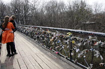 24-03-2012 - A heterosexual young couple kiss on Chortov Bridge, or The Bridge of Love, bridge in a Kiev city park where lovers lock padlocks to the bridge and throw away the key as a symbol of their love and comm... © Janina Struk