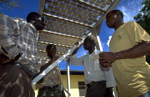 03-07-1997 - Students stand in the shade beneath solar power units at a technical school. Uganda. 1997 © Jim Holmes