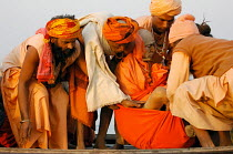 20-02-2007 - Holymen throw the body of their dead friend into the river for burial at the Kumbha Mela festival 2007, the largest gathering of people on the planet. 30 million Hindus and holy men known as Sadhus co... © Tom Parker
