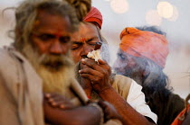 20-02-2007 - A holyman smokes hashish in a pipe at the Kumbha Mela festival 2007, the largest gathering of people on the planet. 30 million Hindus and holy men known as Sadhus come to cleanse their sins in the Gan... © Tom Parker