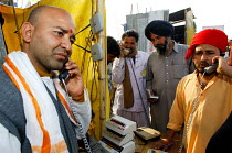 20-02-2007 - Pilgrims at the Kumbha Mela festival 2007 using a public telephone booth, the largest gathering of people on the planet. 30 million Hindus and holy men known as Sadhus come to cleanse their sins in th... © Tom Parker