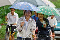 04-04-2007 - Students on bikes shelter from the monsoon rain under umbrellas, Laos. © Tom Parker