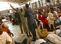11-05-2003 - Reverend John Nduati puts his hand on a woman with HIV to cure her during a service at Gods Power Church and World Center of Healing. In a country where health care is minimal and most cant afford tre... © R. Chalasani