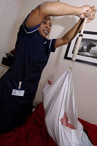26-06-2007 - A midwife weighing a heavy baby on a home visit, Birmingham © Timm Sonnenschein